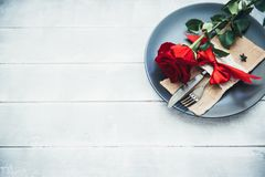 Festive table setting for Valentine`s Day with fork, knife and rose stock photography