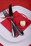 Festive table setting for Valentines Day. Table setting for Valentines Day with white plates,fork,knife,red napkin,ribbon and hearts on red tablecloth Royalty Free Stock Photos
