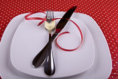Festive table setting for Valentines Day. Table setting for Valentines Day with white plates,fork,knife red ribbon and herds on red tablecloth Royalty Free Stock Photos