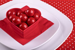 Festive table setting for Valentines Day. Table setting for Valentines Day with white plates,red napkin and red candies in red container shape heart on red Stock Photography