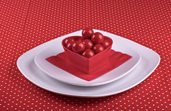 Festive table setting for Valentines Day. Table setting for Valentines Day with white plates,red napkin,red candies in red container shape heart on red Stock Photography