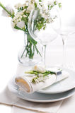 Festive table setting in white. Festive table setting and decoration with fresh flowers in white colors Royalty Free Stock Photography