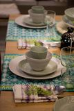 Festive table setting in white and green tones. Plates wine glasses on ethnic napkin with ornament. Beautifully laid table, waiting for guests, tableware stock image