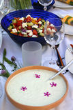 Festive table with tzatziki and colorful salad. A nicely decorated table with wedding glasses and colorful salad with tomatoes and feta cheese Royalty Free Stock Image