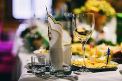 Festive table with wine glasses with napkins and food. For the evening meal in the restaurant royalty free stock photography