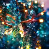 Festive texture in colorful bright turquoise and purple with sprigs, lights, Christmas lights and tinsel stock image