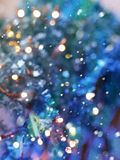 Festive texture in delicate turquoise and purple hues with colorful beautiful bokeh and multi-colored spots and snow royalty free stock photo