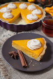 Festive Thanksgiving Homemade Pumpkin Pie with whipped cream, spices and tea Royalty Free Stock Images