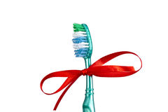 Festive toothbrush with a bow. Festive toothbrush with a red ribbon in a bow form stock photography