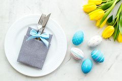 Festive traditional Easter dinner concept. Tableware, painted eggs, tulips flowers on white stone table top view.  royalty free stock photo