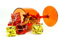 Festive transparent red glass full of small gift-boxes Stock Photos