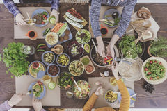 Festive vegetarian table, people eating Stock Photography