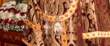 The festive vestments of the Archbishop with a crucifix and a Panagia with an image of the virgin Mary. Adygea, Russia - November 8, 2017: The festive vestments Royalty Free Stock Photos