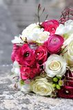 Festive wedding bouquet in grass with two golden rings Royalty Free Stock Images
