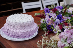 Festive wedding cake and a bouquet of flowers on the table.  Stock Photo