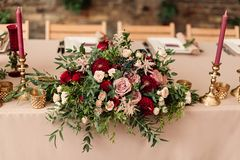 Festive wedding table candle flowers. Festive wedding setting with flowers, napkins, cutlery, glasses, decorative details. The candle in a candlestick chairs and Royalty Free Stock Photos