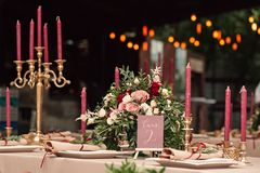 Festive wedding table candle flowers. Festive wedding table setting with flowers, napkins, vintage cutlery, decor details. Candle in a candlestick Royalty Free Stock Images