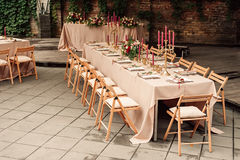 Festive wedding table candle flowers. Festive wedding setting with flowers, napkins, cutlery, glasses, decorative details. The candle in a candlestick chairs and Stock Photo