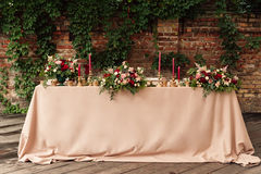 Festive wedding table candle flowers. Festive wedding table setting with flowers, napkins, vintage cutlery, glasses, bright table decor details. Candle in a Royalty Free Stock Photos