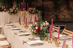 Festive wedding table candle flowers. Festive wedding table setting with flowers, napkins, vintage cutlery, glasses, bright table decor details. Candle in a Royalty Free Stock Image