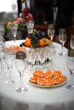 Festive wedding table, glasses of champagne, sandwiches with caviar, snacks, food, pineapples, hearts, love Stock Photos
