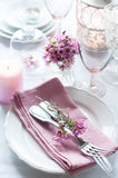 Festive wedding table setting. With pink flowers, napkins, vintage cutlery, glasses and candles, bright summer table decor Stock Photo