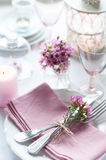 Festive wedding table setting. With pink flowers, napkins, vintage cutlery, glasses and candles, bright summer table decor Stock Images