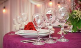 Festive wedding table setting with red flowers, napkins, vintage cutlery, glasses and candles, bright summer table decor stock images