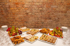 Festive well-laid table with food and drink. On brick wall background Stock Image