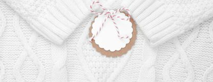 Festive white knitted winter sweater with a label for congratulations. Winter holidays. Banner stock image