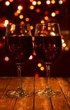 Festive wine glasses with a drink of wine or champagne. On a wooden background with a bokeh for the new year and Christmas Stock Image
