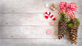Festive Winter Holiday Decor with Copy Space. Festive Winter holiday wood background with ornaments, knitted candy cane and pine-cones with copy space for text Stock Photo