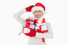 Festive woman scratching head and holding gifts Royalty Free Stock Photography