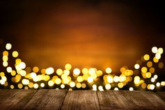 Festive wooden background with glittering lights. Festive wooden background with glittering bokeh lights, illuminated by a spotlight, ideal for Christmas or Royalty Free Stock Photography