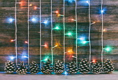 Festive wooden background from old boards with garland and firry cones Royalty Free Stock Photography