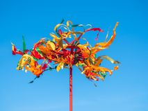 Festive Wooden Pole for Climb on Maslenitsa. Bright ribbons fluttering in the wind. Festive Wooden Pole for Climb on Maslenitsa. Wooden wheel with colorful stock photos