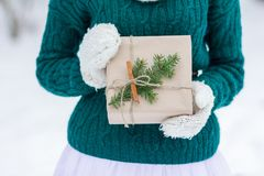 Festive wrapping kraft paper Christmas gift in woolly mittens Royalty Free Stock Photo
