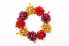 Festive wreath of colorful christmas bows isolated on white. Festive wreath of colorful christmas ribbons isolated on white background Stock Images