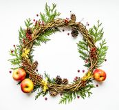 Festive wreath of vines with apples, thuja branches, rowanberries and cones. Flat lay, top view royalty free stock image
