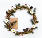 Festive wreath of vines decorated with berries, fir branches, daisy flowers and cones. Flat lay, top view royalty free stock photo