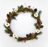Festive wreath of vines decorated with berries, fir branches, daisy flowers and cones. Flat lay, top view stock photo