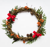 Festive wreath of vines with decorative bows, thuja branches, rowanberries and cones. Flat lay, top view Stock Images
