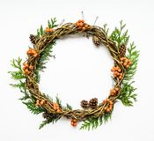 Festive wreath of vines with thuja branches, rowanberries and cones. Flat lay, top view Stock Image
