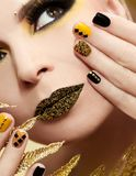 Festive yellow black manicure and makeup . stock photos