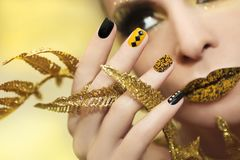 Festive yellow black manicure and makeup . stock image