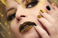 Festive yellow black manicure and makeup . stock images