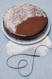 Festivee Cake with chocolate glaze on table served with white crockery Stock Image