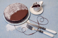 Festivee Cake with chocolate glaze on table served with white crockery Stock Photography