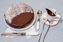 Festivee Cake with chocolate glaze on table served with white crockery Stock Photos
