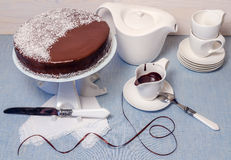 Festivee Cake with chocolate glaze on table served with white crockery Royalty Free Stock Image